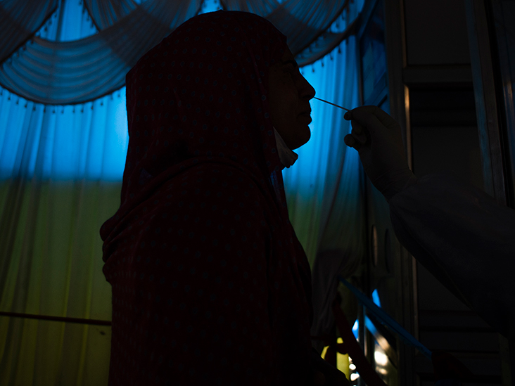 A Kashmiri Muslim girl is silhouetted as a health official uses a nasal swab to collect a sample from her to conduct tests for the coronavirus disease